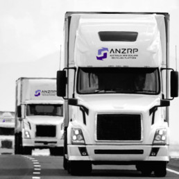 Black and white trucks on a highway with purple ANZRP logo