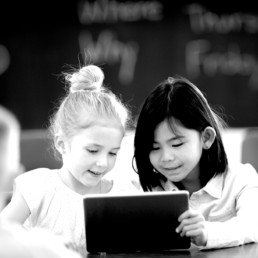Black and white image of two girls using a tablet
