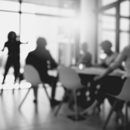 Out of focus black and white image of a team collaborating in a meeting room