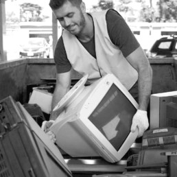 Man lifting old computer from skip bin for recycling