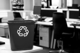 Out of focus image of office cubicles with a recycling bin in focus in the foreground