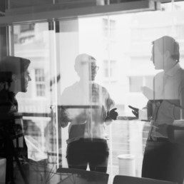 Four people collaborating and talking together in a bright meeting room