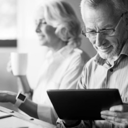 Older couple having a cup of tea and looking at a tablet