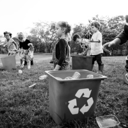 Kids running around collecting plastic bottles and putting them in recycle bins